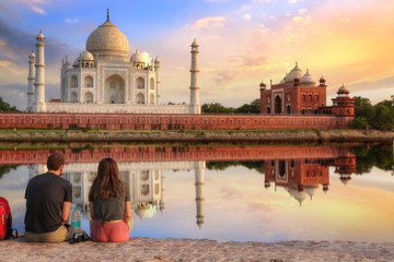 Wall Mural - Taj Mahal Agra at sunset with moody sky and water reflection enjoyed by tourist couple sitting at Mehtab Bagh beside river Yamuna