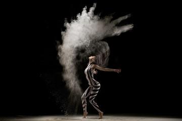 Graceful girl dancing in dust cloud in the dark