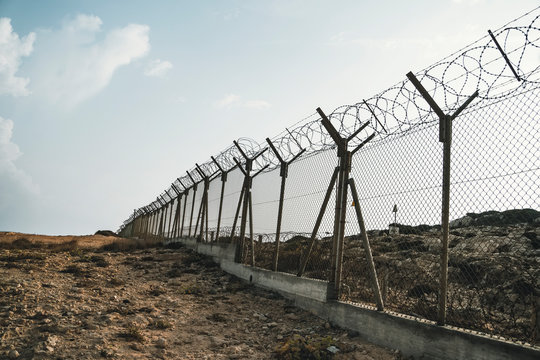 barbed wire steel wall against the immigations. Wall with barbed wire on the border of 2 countries. Private or closed military zone.
