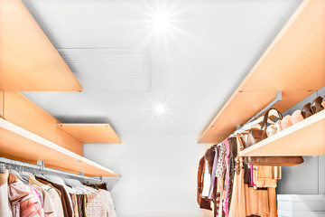 Modern clothing store with wooden shelves and lots of dresses