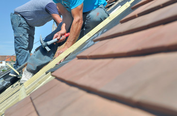 roofers working at the top of a house  for renovation
