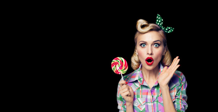 Photo of beautiful very surprised woman with lollipop, in pinup style, over black color background