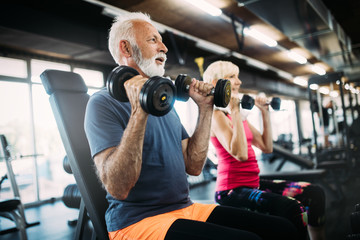 Happy senior people doing exercises in gym to stay fit