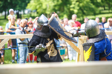 medieval jousting knight fight, in armor, helmets, chain mail with axes and swords on lists. historic reconstruction of ancient fight