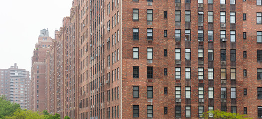 Fototapete - New York, Manhattan Chelsea area. Brick wall facade skyscrapers against cloudy sky background