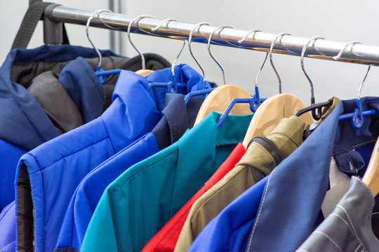 The upper work clothes of strong fabric of different colors with pockets hang on the hangers as a sample