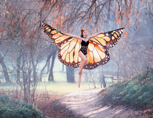 a joyful girl with big bright orange wings walks in the early trenched spring forest, warm positive emotions, happy flight of a moth, bright young green grass and yellow trees, sun rays
