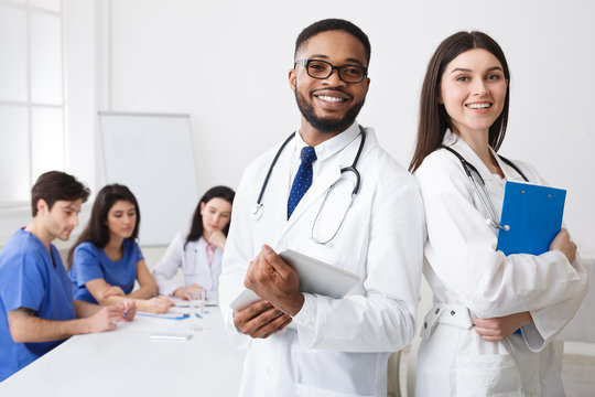 Diverse Professional Doctors In White Coats Posing To Camera At