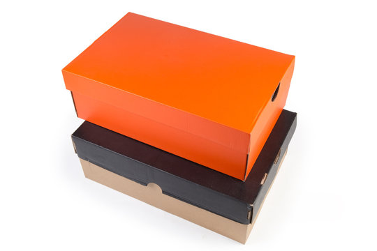 Closed black and orange cardboard shoe boxes on white background