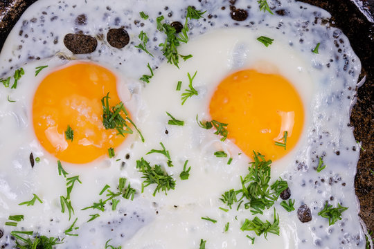 Top view of two fried eggs on the frying pan