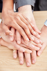 Business people stack hands as a sign for teambuilding