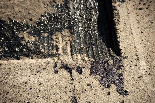 Tire tracks on bitumen on the surface of asphalt under construction