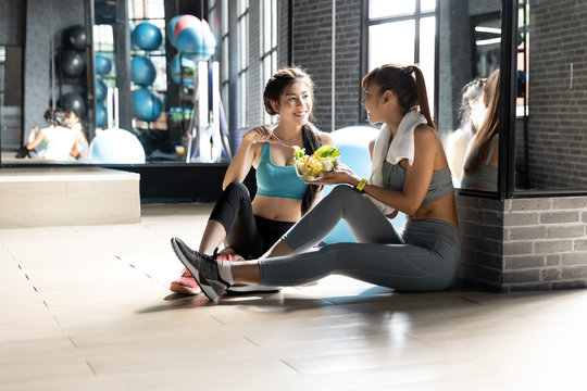 Healthy asian two people young woman eating vegetables green salad at gym In a room with a window with natural light. Fitness and healthy food concept