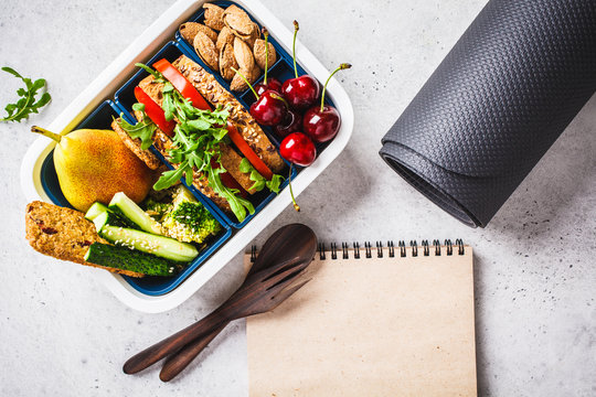 Sport food concept. Lunch box with heathy food, notebook and mat on a gray background.
