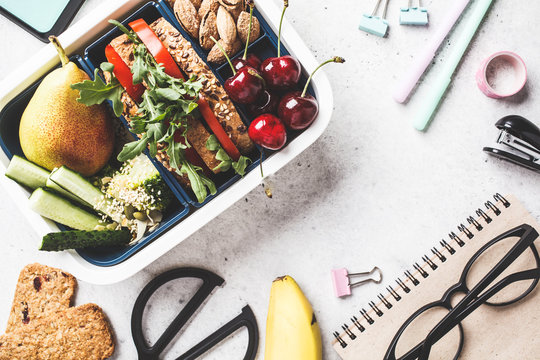 Back to school concept.  Lunch box with sandwich, fruit, snacks, notebook, pencils and school items, top view.