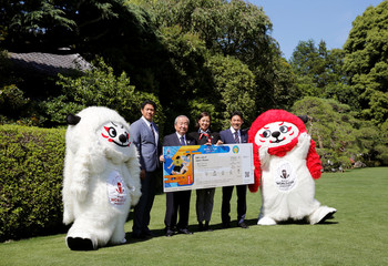 Ren and G, official mascots for the 2019 Rugby World Cup in Japan, pose with officials during a photo session during the unveiling of the ticket design in Tokyo