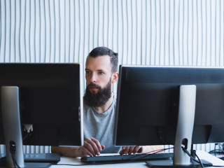 Quality assurance. Bearded software engineer using two monitors, working on task at office. Copy space.