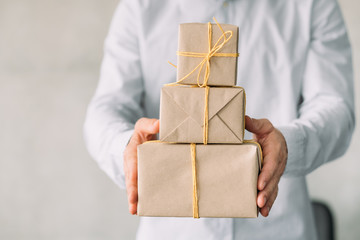 Corporate party. Online gift shop. Cropped shot of business man holding paper wrapped boxes. Gray wall background. Copy space.