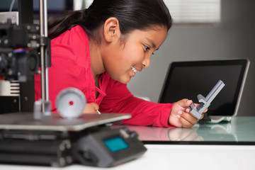 A smiling young girl is happy to see her 3d printed model and is holding it in her hand with a 3d printer in foreground and touchscreen in background.