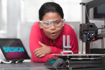An young hispanic girl is amazed as she looks at her 3d printed project in a STEM summer class.