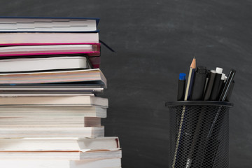 Education concept. Closeup of book stack, stationery over empty black chalkboard. Copy space.