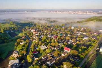 View from above of white fog on village house roofs among green trees under bright blue sky. Spring misty landscape panorama at dawn. Fototapete