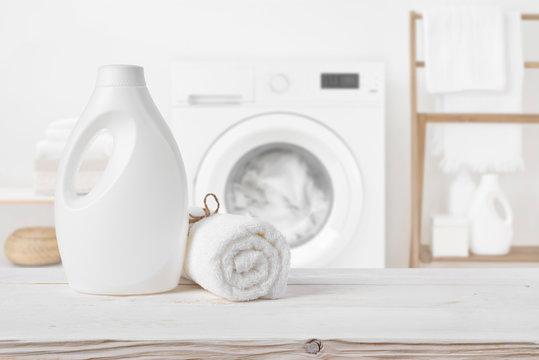 Plain detergent bottle on wood over defocused laundry room interior