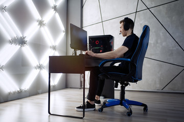 Professional gamer in his expensive studio young man having live stream playing online video game. Cyber sportsman is streaming popular pc computer game for his followers