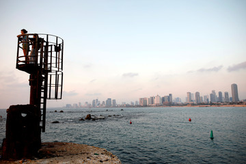 People stand on a watchtower at the end of a jetty in the Mediterranean Sea as Tel Aviv's skyline of high-rise buildings is seen in the background, in Jaffa, Israel