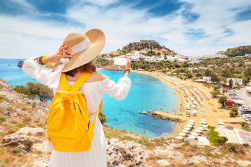Young and happy woman tourist taking selfie photo on her smartphone with view on a sandy beach and old town. Vacaction and travel concept