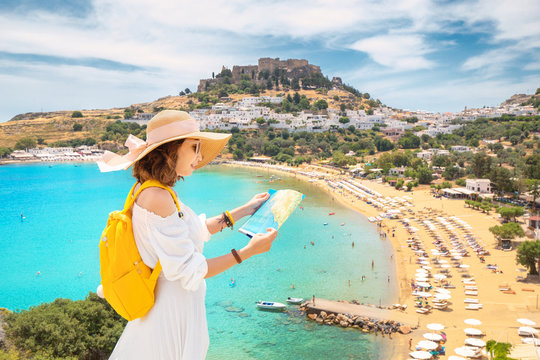 Happy asian woman with map and backpack wearing big vacation hat at the background of paradise view to Lindos town and beach on a Rhodes Island, Greece