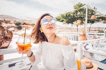 Happy asian woman enjoying aperol spritz cocktail in a greek cafe. Beverage and refreshment concept