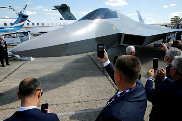Visitors take pictures of the one-to-one mock-up of a Turkish fighter aircraft by Turkish Aerospace unveiled during the 53rd International Paris Air Show at Le Bourget Airport near Paris