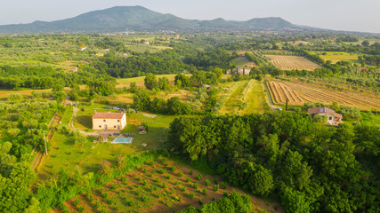 Aerial view on the Irpinia countryside in the province of Avellino, Italy. Among the cultivated fields and woods in the mountains there is some isolated house.