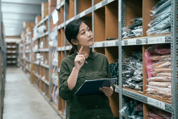 young attractive asian woman auditor staff work looking up stocktaking inventory in warehouse store. lady worker in clothes shop factory working with clipboard and pen. girl point at shelf counting.