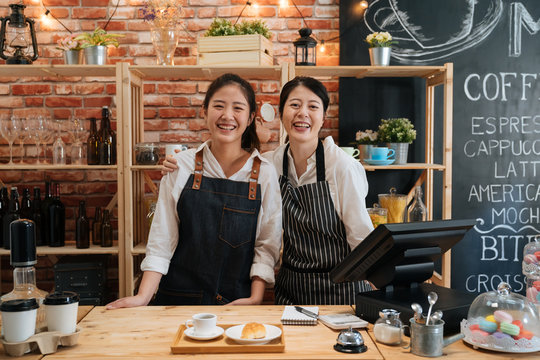 Small startup business owner concept. two successful young baristas women standing in bar counter in cafe. happy coffeehouse waitresses in aprons smiling confidently to camera in coffee shop.