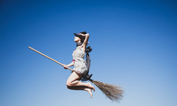 Young redhead witch on broom flying in the sky