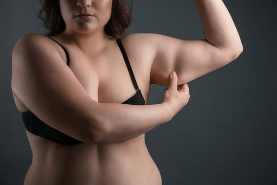 Beautiful plus size woman on grey background. Concept of weight loss