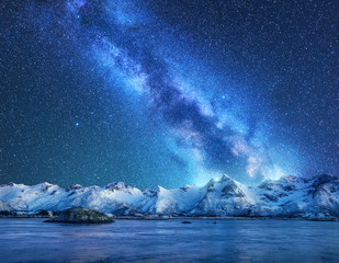 Obraz Bright Milky Way over snow covered mountains and sea at night in winter in Norway. Landscape with snowy rocks, starry sky, reflection in water, fjord. Lofoten Islands. Space. Beautiful milky way - fototapety do salonu