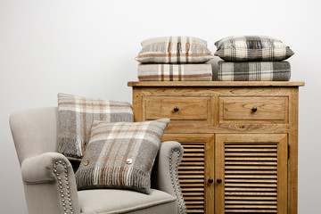 Chair and side cabinet with natural coloured checked cushions and throws. Wall mural