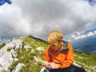 Female hiker reading a map on top of the Mountain