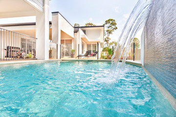 Swimming pool in house front side near garden.