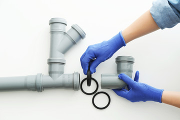 Plumber working with drain pipe on white background