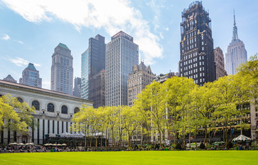 Bryant park, New York, Manhattan. High buildings view from below against blue sky background, sunny day in spring