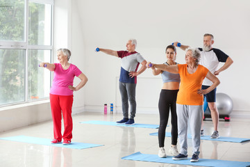 Elderly people training with instructor in gym