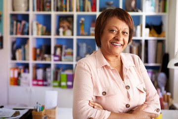 Portrait Of Smiling Mature Woman In Home Office By Bookcase