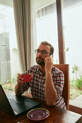 Modern bearded man using cellphone and drinking coffee with laptop.