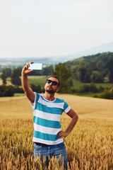 Trendy man using cellphone in nature.