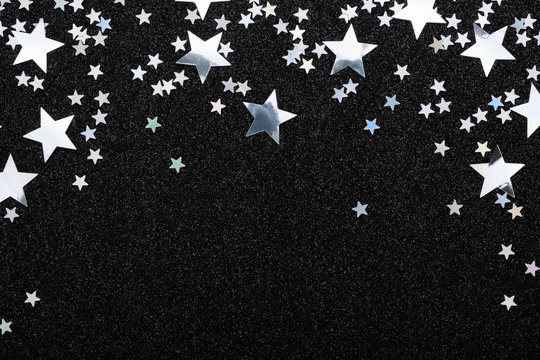 Falling silver stars confetti on black Festive holiday background. Glowing sparkles frame, flat lay, copy space.