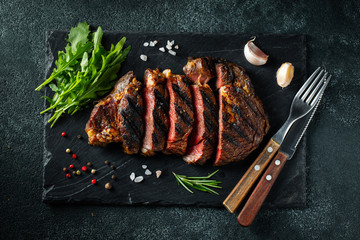 Printed kitchen splashbacks Steakhouse Sliced steak ribeye, grilled with pepper, garlic, salt and thyme served on a slate chopping Board on a dark stone background. Top view. Flat lay
